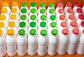 Dairy products bottles with bright covers on a shelf in the shop — Stock Photo