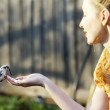 The young beautiful woman feeds a bird from a hand, focus on a bird — Stock Photo #70902539