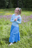 The beautiful young woman in a blue dress in the field — Stock Photo
