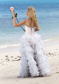 The young beautiful woman in a dress of the bride on sand at sea edge — Stock Photo