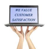 """Notebook wit Text """"Wir legen Wert auf die Zufriedenheit der Kunden"""" — Stockfoto"""