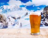 Glass of beer over winter landscape — Stock Photo