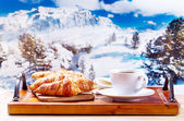 Cup of coffee and croissants over winter landscape — Stock Photo