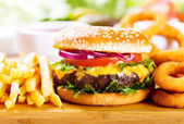 Hamburger with fries and onion rings — Stock Photo