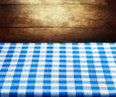 Checkered blue tablecloth over wooden background — Stock Photo