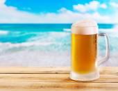 Krug Bier auf Holztisch über Meer — Stockfoto
