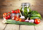 Preserved tomatoes and cucumbers with fresh vegetables — Stock Photo