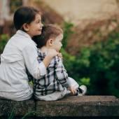 Pequeña hermana y hermano abrazando — Foto de Stock