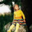 Little girl sitting on big stone — Stock Photo #53829499