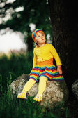 Little girl sitting on big stone — ストック写真