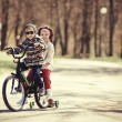 Little girl and boy riding on bicycle together — Stockfoto #53837077