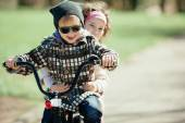Little girl and boy riding on bicycle together — ストック写真