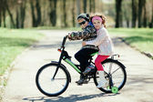 Little girl and boy riding on bicycle together — Foto de Stock