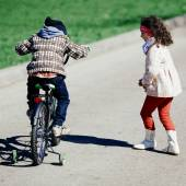 Little girl run to small boy on bicycle — Stockfoto