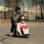 Boy and girl skating on the street — Stock Photo