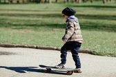 Little boy with skateboard on the street — ストック写真