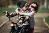 Little boy and girl ride bike — Stock Photo
