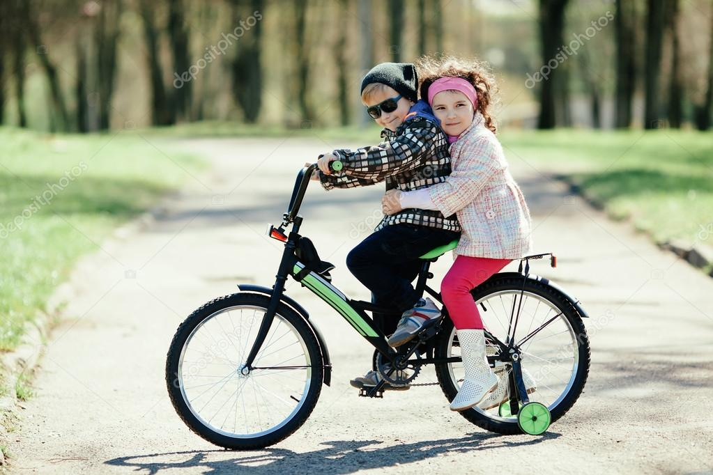 Niña Feliz Andar En Bicicleta: Niña Y Niño Andando En Bicicleta Juntos