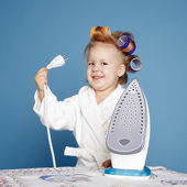 Little housewife with iron on blue background — Stock Photo
