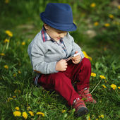 Boy with phone sitting on grass — Stock Photo