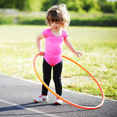 Little girl learns to spin the Hoop — Stock Photo