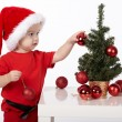 Boy with Santa hat decorates christmas tree — Stock Photo #54900487