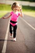Ittle cute girl running at stadium — Stock Photo