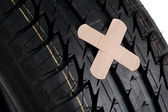 Black new tire with patch on white — Stock Photo