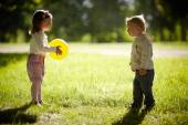 Boy and girl playing with yellow ball — Stock Photo