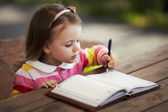 Cute little girl learning to write — Stockfoto