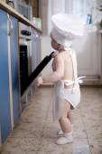Baby chef cooks in the oven food — Stock fotografie