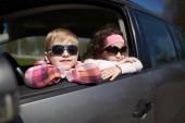 Girl and boy driving fathers car — Stock Photo