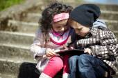 Boy and girl using tablet together — Stock Photo