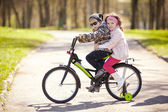 Girl and boy riding on bicycle — Stock Photo