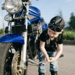 Постер, плакат: Little biker repairs motorcycle on road