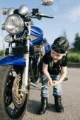 Little biker repairs motorcycle on road — Stock Photo