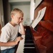 Boy plays piano at home — Stock Photo #79796994