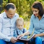 Family reading book in park — Stock Photo #79936962
