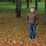 Little funny boy in autumn leaves portrait — Stock Photo #80155156