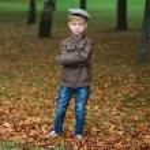 Little funny boy in autumn leaves portrait — Stock Photo #80155612