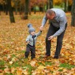 Father with son walking in autumn forest — Stock Photo #80702498