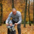Father with son walking in autumn forest — Stock Photo #80703366