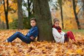 Boy and girl in autumn park — Stock Photo