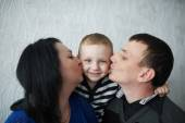 Mom and dad kiss son — Stock Photo