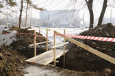 Wooden bridge over dug trench. — Stock Photo