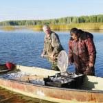 Fishermen with catch of fish coregonus — Stock Photo #71592933