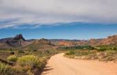 Dirt road leading over high mountain pass in daytime — 图库照片