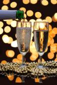 Two champagne glasses with bubbles and bokeh lights in the back — Stock Photo