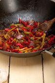 Fried chili pepper and vegetable on a wok pan — Stock Photo