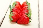 Fresh organic strawberry over white wood — Stock Photo